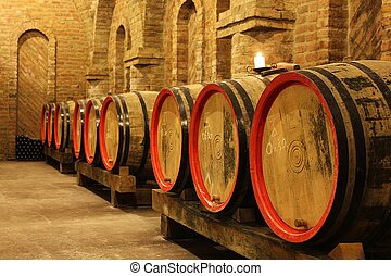 wine barrels in cellar - wine barrels and bottles in a...