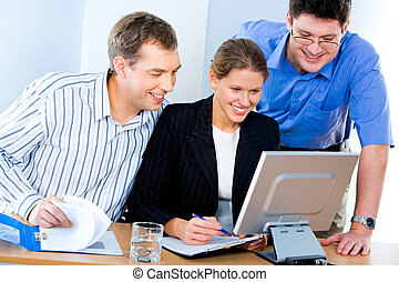 Computer work - Portrait of three business partners doing...