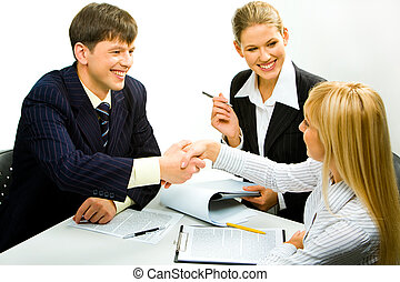 Greeting - Portrait of two happy business partners shaking...