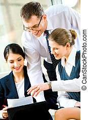 Reading business documents - Group of three co-workers...