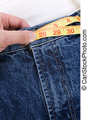 weight loss - a blue jean and ruler, concept of weight loss