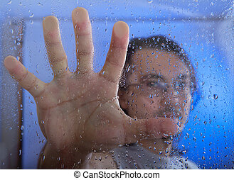 young man standing near the window with rain drops - young...
