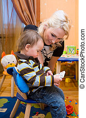 The education - blondy mother educating her son sitting in...