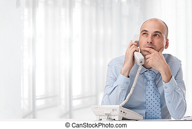 Businessman talking on landline phone at office - Young...