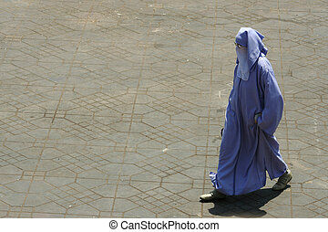 Muslin Woman - Muslin woman with traditional vests, walking...
