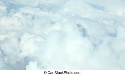 Airplane flying above puffy clouds - View from airplane