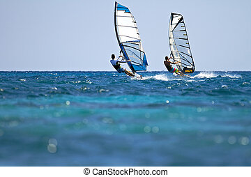 Two windsurfers in action - Back view of two windsurfers in...