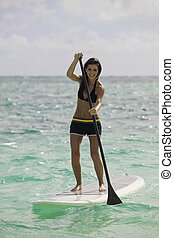woman with her paddle board at a hawaii beach