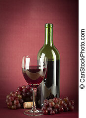 Wine Bottle and Glass - A bottle of red wine, a glass half...