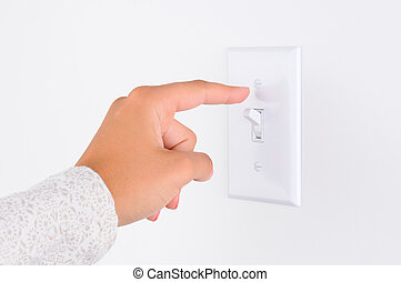 Woman Turning Out the Lights - Womans hand with finger on...