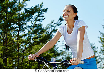 Riding a bicycle - Pretty young woman riding a bicycle