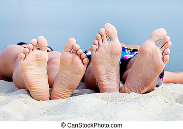 Getaway - Soles of teenagers sunbathing on sandy beach