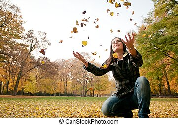 Happy life - woman throwing leaves in fall - Lifestyle...