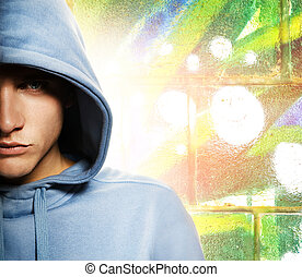 Cool looking man in a hood over abstract graffity background