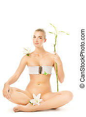 Relaxed young woman with white lily and bamboo plant....