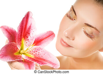 Beautiful young woman with pink lily close-up portrait...