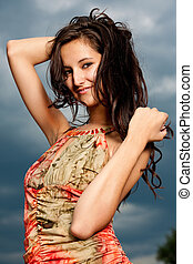 Beauty brunette posing over dark sky background - Beauty...
