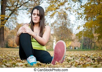 Knee injury - woman sitting in pain - Sport injury - young...
