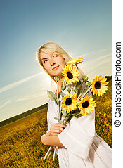 Young beautiful woman with a bouquet of sunflowers in the...