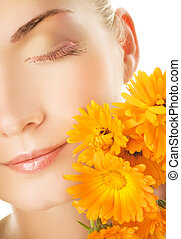 Beautiful young woman's face with orange flowers