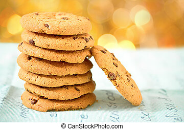 chocolate chip cookies on blue table set with bokeh...