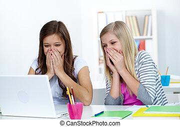 Joke - Two laughing girls looking at laptop screen in...