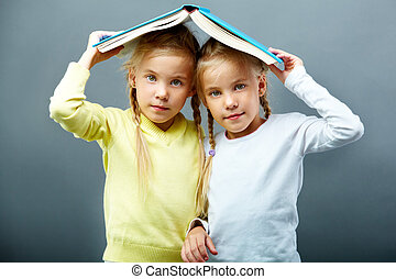 Twins under book - Portrait of lovely twin girls holding...