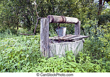 Old countryside water well with a bucket.