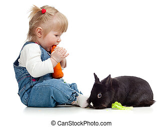Smiling little girl eating a carrot and feeding rabbit with...