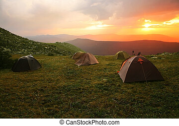 landscape with sunset and tents on glade - Mountain...