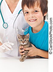Boy getting his kitten to vaccination at the veterinary