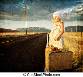 Young girl on side of road with suitcases