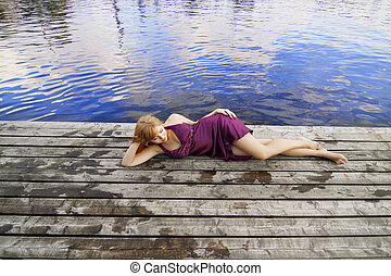 Beautiful red-haired girl on the pier in a purple dress -...