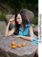 Beautiful young girl with the mandarins in nature - The...