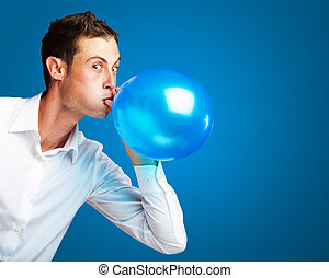 Portrait Of Young Man BlowingBalloon On Blue Background