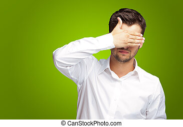 Portrait Of An Businessman Covering Eyes Isolated On Green...