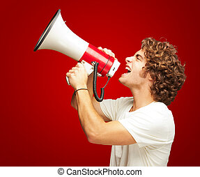 Portrait Of Young Man Shouting With A Megaphone - Portrait...