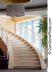 Modern staircase in hotel foyer with daylight from window