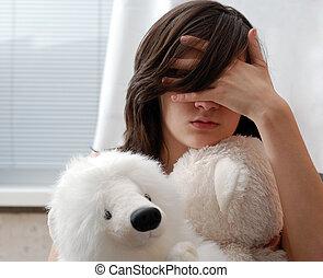 Teenage girl with teddy bear, face hidden with hand -...