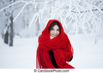 Beautiful girl in winter forest in red - The image of a...
