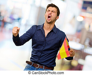 Man cheering and holding flag - Man cheering and holding...