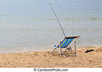 Fishing rod is placed beside the chair beach