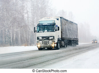 truck goes on winter road to blizzard