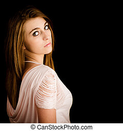 Portrait of beautiful teenage girl with serious expression isolated on black with room for copy