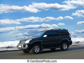 SUV goes on winter road against clear cloudy sky