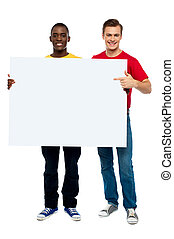 Smiling guys with white ad board - Young man pointing at...