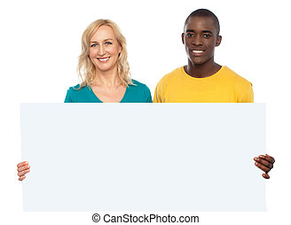 Attractive couple holding white blank ad board looking at...
