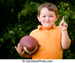 Child with football celebrating by showing that he's Number...