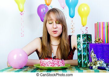 Birthday. An attractive young girl blows out the candle on...