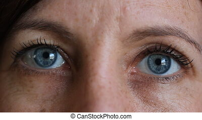 Staring blue eyes. - Woman with striking blue eyes stares at...